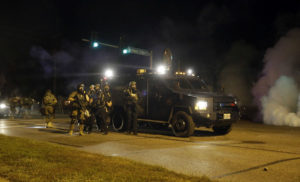 Police in riot gear work to disperse a crowd of protesters in Ferguson, Mo., August 2014. THE ASSOCIATED PRESS