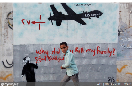 A Yemeni boy walks past a mural depicting a US drone on December 13, 2013 in the capital Sanaa.