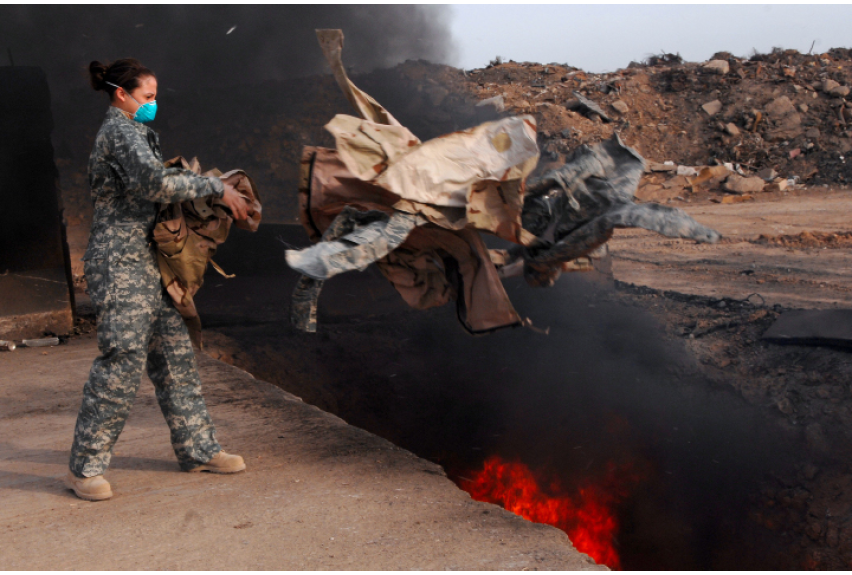 Senior Airman Frances Gavalis tosses unserviceable military uniform items into a burn pit at Balad Air Base, Iraq